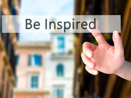 inspired: Be Inspired - Hand pressing a button on blurred background concept . Business, technology, internet concept. Stock Photo Stock Photo