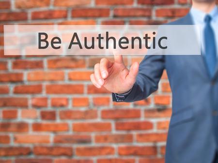 Soyez authentique - bouton sur l'interface de l'écran tactile d'affaires main pressant. Affaires, technologie, internet concept. photo