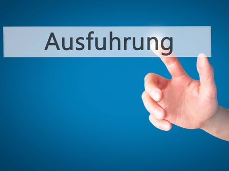 execution: Ausfuhrung (Execution in German) - Hand pressing a button on blurred background concept . Business, technology, internet concept. Stock Photo Stock Photo