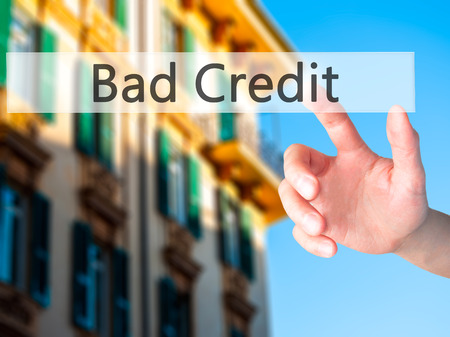 creditworthiness: Bad Credit - Hand pressing a button on blurred background concept . Business, technology, internet concept. Stock Photo