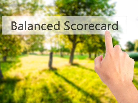 balanced budget: Balanced Scorecard - Hand pressing a button on blurred background concept . Business, technology, internet concept. Stock Photo Stock Photo