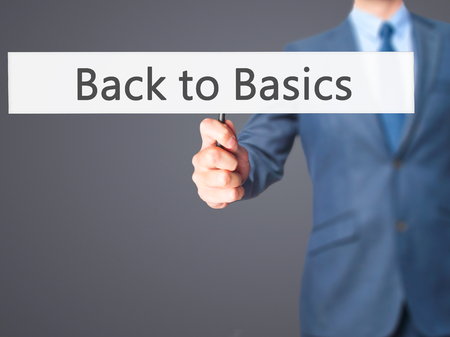 basics: Back to Basics - Business man showing sign. Business, technology, internet concept. Stock Photo