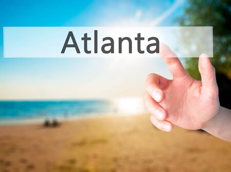 Atlanta - Hand pressing a button on blurred background concept . Business, technology, internet concept. Stock Photo