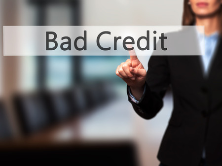 creditworthiness: Bad Credit - Businesswoman hand pressing button on touch screen interface. Business, technology, internet concept. Stock Photo Stock Photo