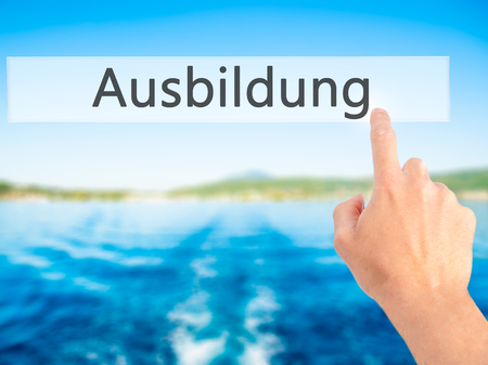 Ausbildung (Education in German) - Hand pressing a button on blurred background concept . Business, technology, internet concept. Stock Photo