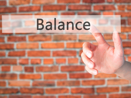 sense of security: Balance - Hand pressing a button on blurred background concept . Business, technology, internet concept. Stock Photo