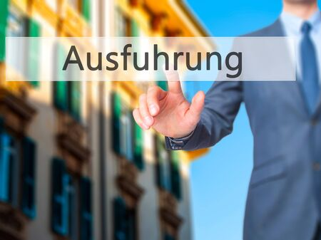 execution: Ausfuhrung (Execution in German) - Businessman hand pressing button on touch screen interface. Business, technology, internet concept. Stock Photo Stock Photo