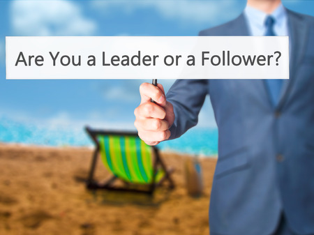Are You a Leader or a Follower ? - Business man showing sign. Business, technology, internet concept. Stock Photo Stock Photo