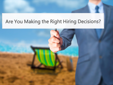 Are You Making the Right Hiring Decisions ? - Business man showing sign. Business, technology, internet concept. Stock Photo