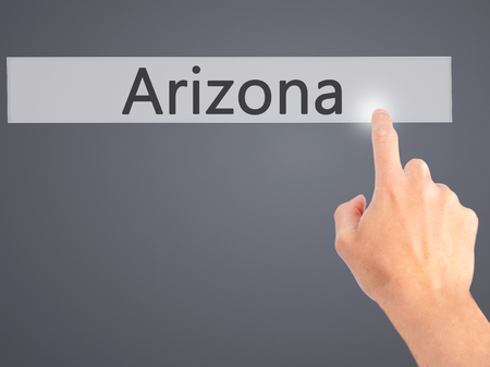 stone of destiny: Arizona - Hand pressing a button on blurred background concept . Business, technology, internet concept. Stock Photo