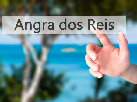 accommodating: Angra dos Reis - Hand pressing a button on blurred background concept . Business, technology, internet concept. Stock Photo