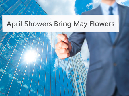 april showers: April Showers Bring May Flowers - Business man showing sign. Business, technology, internet concept. Stock Photo