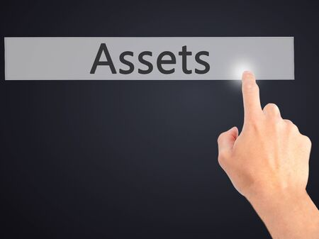 digital asset management: Assets - Hand pressing a button on blurred background concept . Business, technology, internet concept. Stock Photo Stock Photo