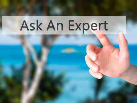 Ask An Expert - Hand pressing a button on blurred background concept . Business, technology, internet concept. Stock Photo