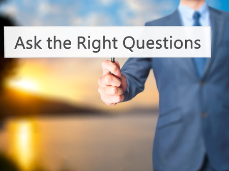 enterprising: Ask the Right Questions - Business man showing sign. Business, technology, internet concept. Stock Photo