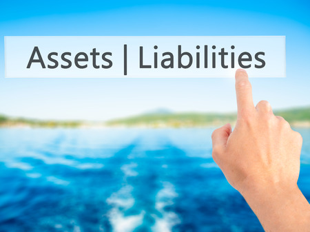 cash flow statement: Assets Liabilities - Hand pressing a button on blurred background concept . Business, technology, internet concept. Stock Photo Stock Photo
