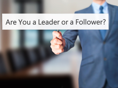 dutiful: Are You a Leader or a Follower ? - Business man showing sign. Business, technology, internet concept. Stock Photo Stock Photo