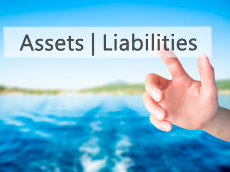 Assets Liabilities - Hand pressing a button on blurred background concept . Business, technology, internet concept. Stock Photo Stock Photo
