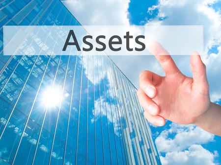 recursos financieros: Assets - Hand pressing a button on blurred background concept . Business, technology, internet concept. Stock Photo Foto de archivo
