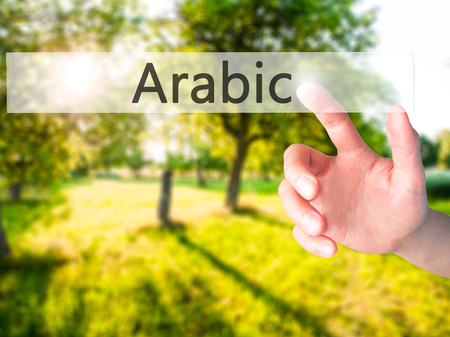 Arabic - Hand pressing a button on blurred background concept . Business, technology, internet concept. Stock Photo