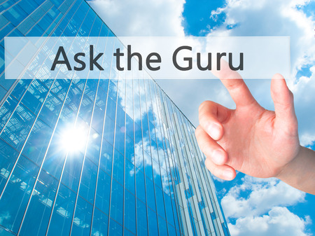 Ask the Guru - Hand pressing a button on blurred background concept . Business, technology, internet concept. Stock Photo