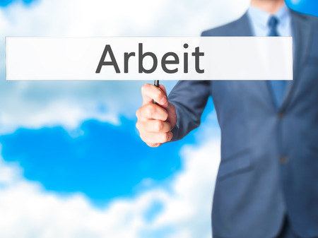 Arbeit (Work in German) - Business man showing sign. Business, technology, internet concept. Stock Photo Stock Photo