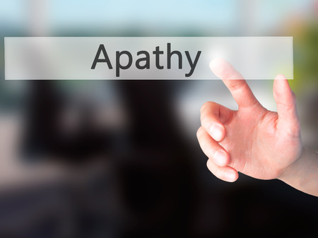 ambiguous: Apathy - Hand pressing a button on blurred background concept . Business, technology, internet concept. Stock Photo
