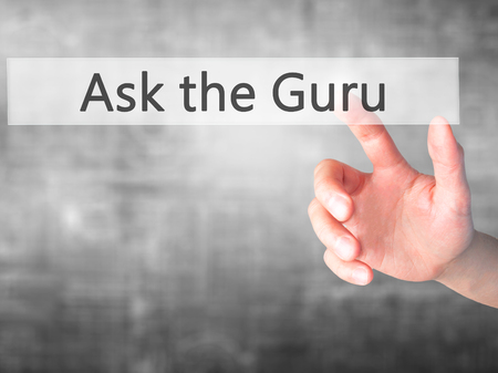stock market launch: Ask the Guru - Hand pressing a button on blurred background concept . Business, technology, internet concept. Stock Photo
