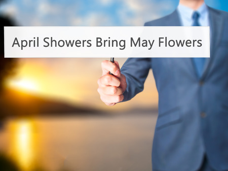 bring: April Showers Bring May Flowers - Business man showing sign. Business, technology, internet concept. Stock Photo