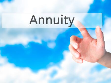 Annuity - Hand pressing a button on blurred background concept . Business, technology, internet concept. Stock Photo