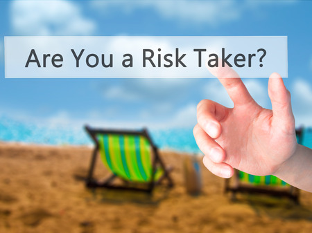 taker: Are You a Risk Taker ? - Hand pressing a button on blurred background concept . Business, technology, internet concept. Stock Photo