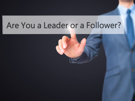 dutiful: Are You a Leader or a Follower ? - Businessman press on digital screen. Business,  internet concept. Stock Photo