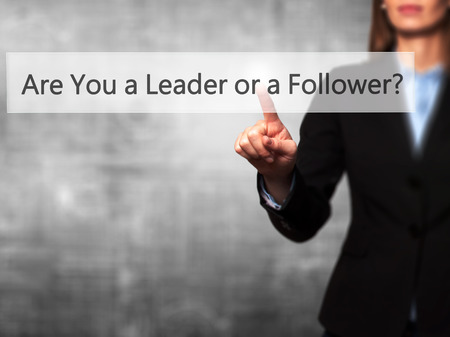 blindly: Are You a Leader or a Follower ? - Isolated female hand touching or pointing to button. Business and future technology concept. Stock Photo