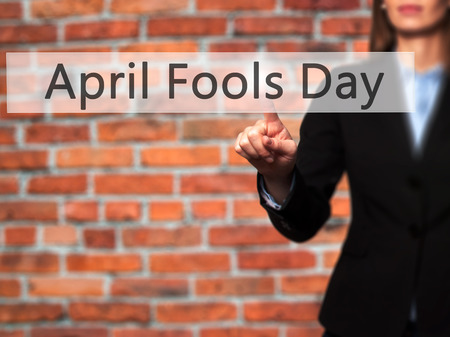 prank: April Fools Day - Isolated female hand touching or pointing to button. Business and future technology concept. Stock Photo Stock Photo