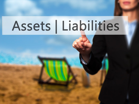Assets Liabilities - Isolated female hand touching or pointing to button. Business and future technology concept. Stock Photo