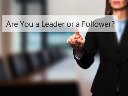 constrained: Are You a Leader or a Follower ? - Isolated female hand touching or pointing to button. Business and future technology concept. Stock Photo