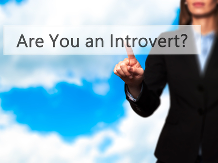 outspoken: Are You an Introvert ? - Isolated female hand touching or pointing to button. Business and future technology concept. Stock Photo