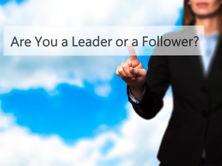 dutiful: Are You a Leader or a Follower ? - Isolated female hand touching or pointing to button. Business and future technology concept. Stock Photo
