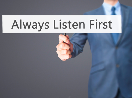 always: Always Listen First - Businessman hand holding sign. Business, technology, internet concept. Stock Photo