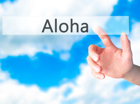 Aloha - Hand pressing a button on blurred background concept . Business, technology, internet concept. Stock Photo