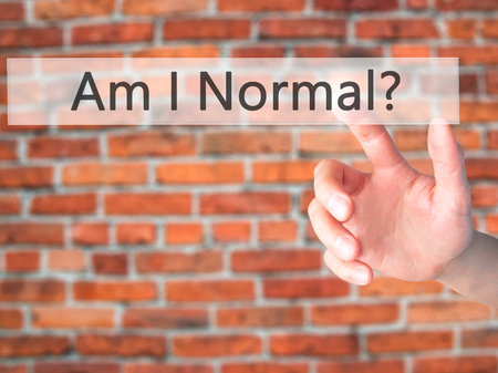 Am I Normal ? - Hand pressing a button on blurred background concept . Business, technology, internet concept. Stock Photo