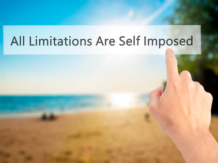 imposed: All Limitations Are Self Imposed - Hand pressing a button on blurred background concept . Business, technology, internet concept. Stock Photo