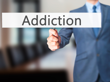 reclamation: Addiction - Businessman hand holding sign. Business, technology, internet concept. Stock Photo