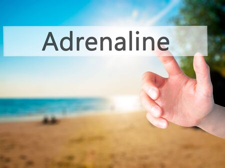 adrenaline rush: Adrenaline - Hand pressing a button on blurred background concept . Business, technology, internet concept. Stock Photo