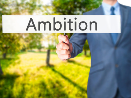 leadership potential: Ambition - Businessman hand holding sign. Business, technology, internet concept. Stock Photo