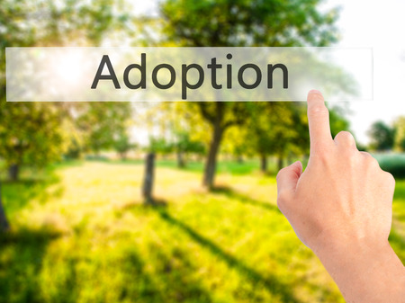 mother in law: Adoption - Hand pressing a button on blurred background concept . Business, technology, internet concept. Stock Photo Stock Photo