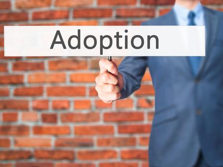 adopting: Adoption - Businessman hand holding sign. Business, technology, internet concept. Stock Photo Stock Photo