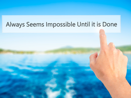 unachievable: Always Seems Impossible Until it is Done - Hand pressing a button on blurred background concept . Business, technology, internet concept. Stock Photo