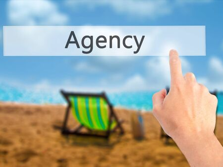 stock agency: Agency - Hand pressing a button on blurred background concept . Business, technology, internet concept. Stock Photo Stock Photo