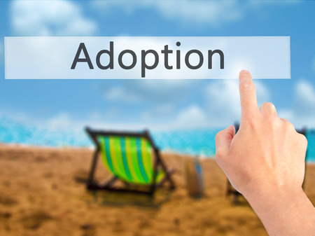 Adoption - Hand pressing a button on blurred background concept . Business, technology, internet concept. Stock Photo Stock Photo